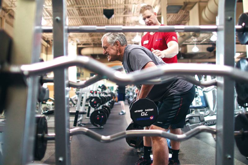 by: TRIBUNE PHOTOS: JAIME VALDEZ - Portland Mayor Charlie Hales, who works out regularly at 24 Hour Fitness, does a bent-over-row exercise with personal trainer Steven Brock.