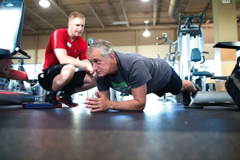 by: TRIBUNE PHOTO: JAIME VALDEZ - Portland Mayor Charlie Hales does a plank exercise during one of his regular morning sessions at 24 Hour Fitness, as personal trainer Steven Brock checks his form.