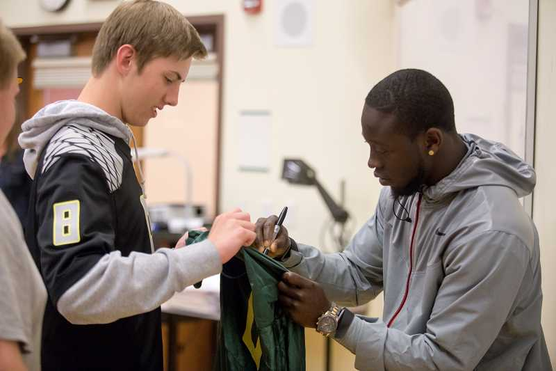 by: TIMES PHOTO: JONATHAN HOUSE  - Beaverton High student Rob Lavey gets an Oregon Ducks jersey autographed by De'Anthony Thomas during a talk in his marketing class on Monday.