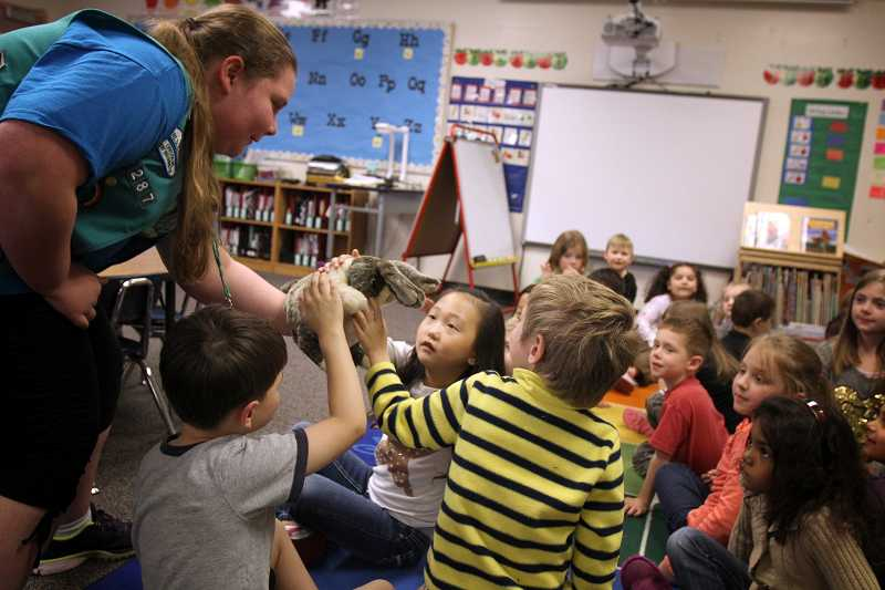 by: TIMES PHOTO: JONATHAN HOUSE - Rock Creek Elementary School kindergartners pet Ready Rabbit, the designated expert on winter weather emergencies, during a puppet presentation by Girl Scout Juniors at the school.
