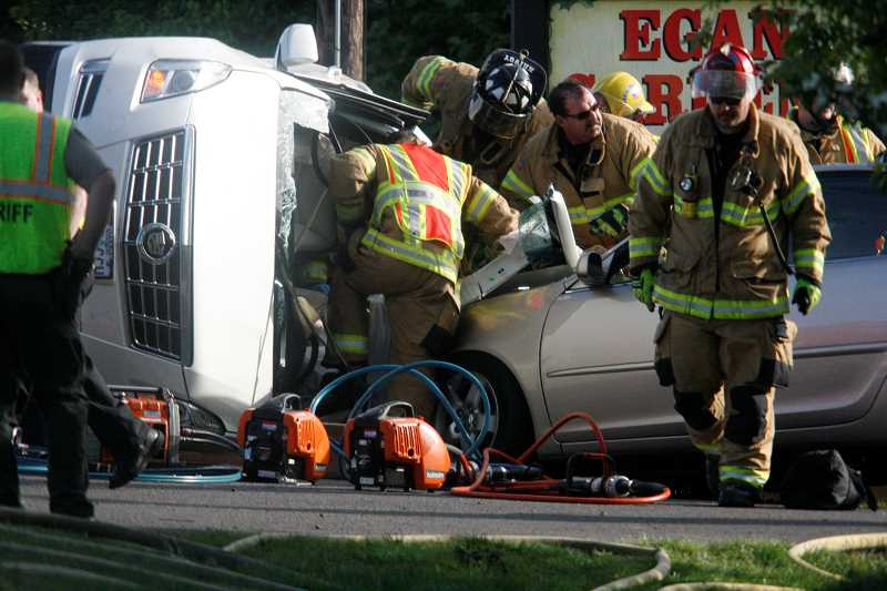 by: PHIL HAWKINS - First responders use the Jaws of Life to extricate victims of a three-car crash from a Lincoln Navigator Wednesday.