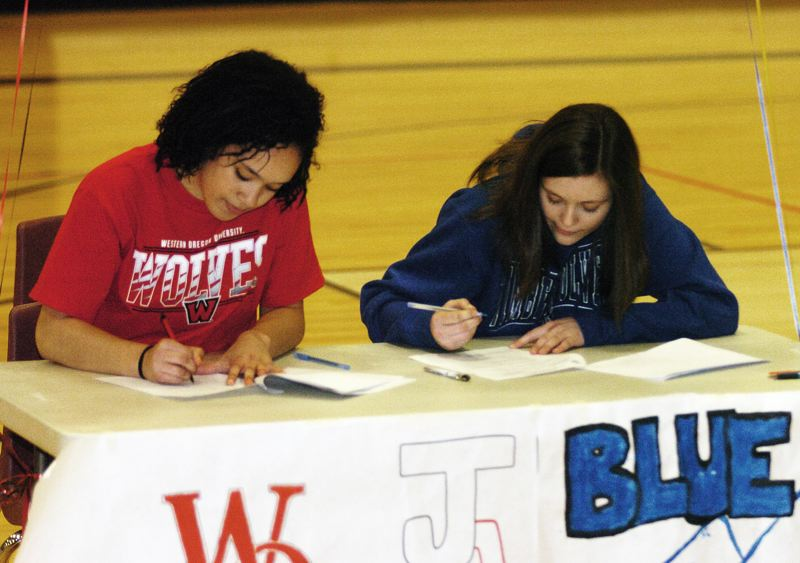 by: DAN BROOD - ON THE DOTTED LINE -- Tualatin High School seniors Jasmine Miller (left) and Savannah Heugly sign their letters of intent during a ceremony held at the school.