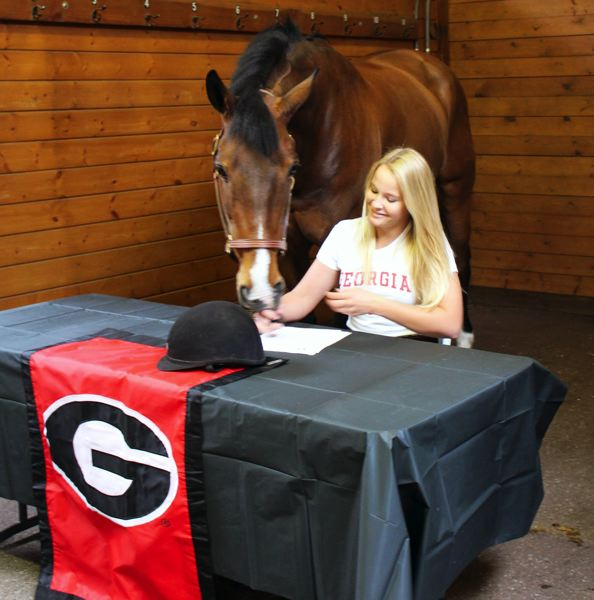 by: SUBMITTED PHOTO - HORSE SENSE -- Tualatin High School senior Kelly Skoglund, with her horse, Soldier Boy, at her side, signs her letter of intent to attend the University of Georgia.