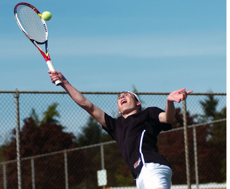 by: DAN BROOD - REACHING -- Tualatin sophomore Ryan Malinowski gets up high to hit the ball in his No. 1 singles match against Tigard junior Nick Evans. Malinowski got a 6-4, 6-2 victory.