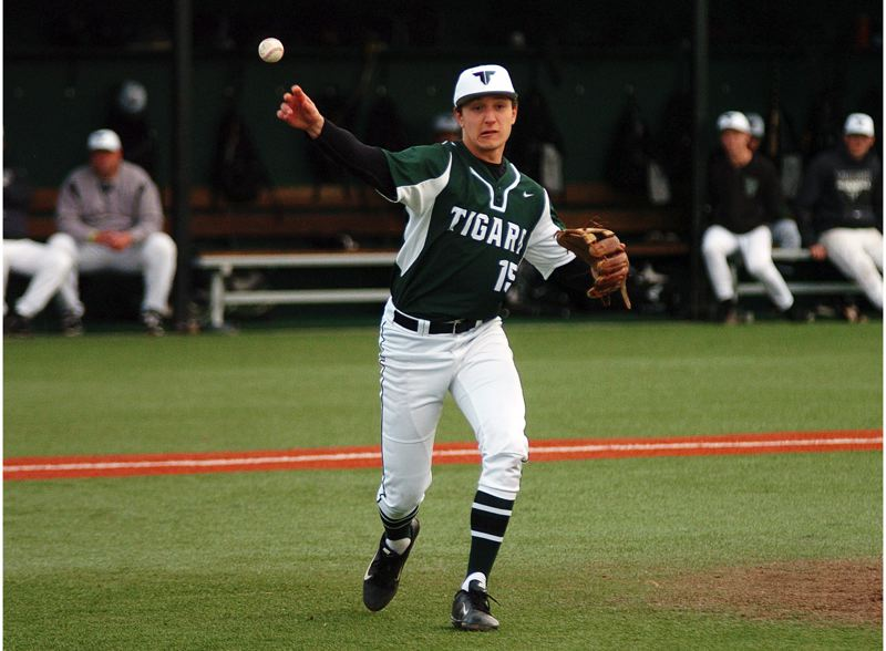 by: DAN BROOD - MAKING THE PLAY -- Tigard High School senior pitcher Nick Duron makes a throw to first base after fielding a grounder in last week's game with Century. Duron pitched the Tigers to a 3-0 victory.
