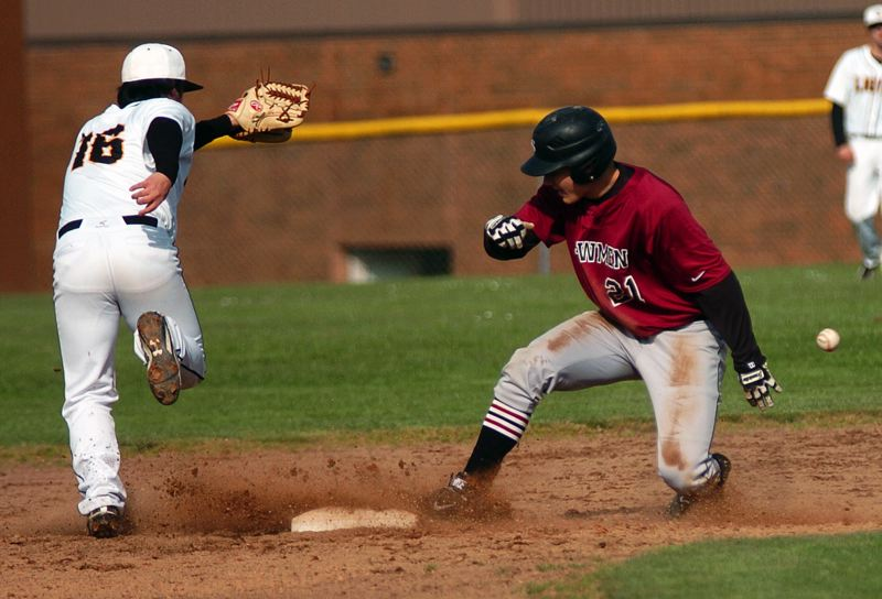 by: DAN BROOD - SWIPING -- Sherwood senior Keegan Lawrence (21) steals second base during the Bowmen's win at St. Helens on Monday. Lawrence also went on to steal third base.