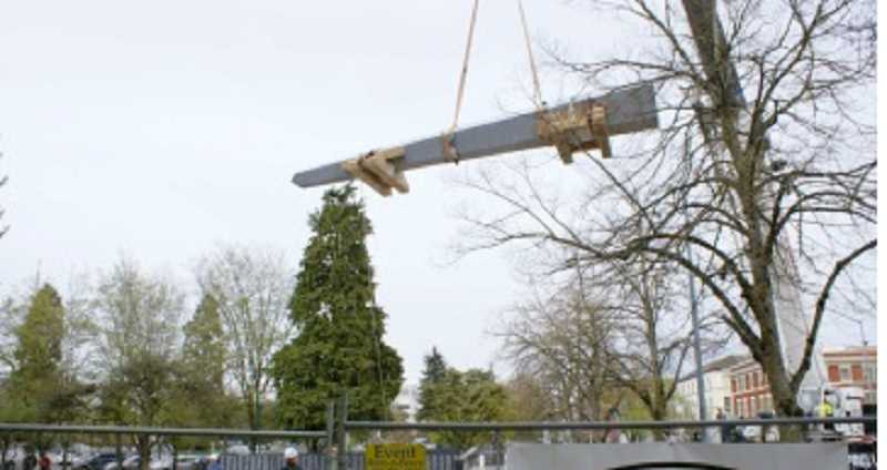 by: COURTESY OF OREGON DEPARTMENT OF VETERANS AFFAIRS - HIGH-FLYING MANEUVER - Under the watchful eyes of construction workers, a crane slowly moves the 20-ton obelisk into place at the Oregon World War II Memorial.