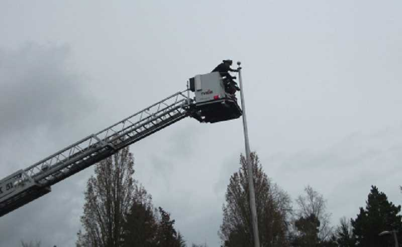 by: SHARON HUGHES/FOR THE REGAL COURIER - ALL IN A DAY'S WORK - A crew from Tualatin Valley Fire & Rescue Station 51 in Tigard uses its ladder truck and bucket to install a new halyard on the flagpole outside the Summerfield Clubhouse.