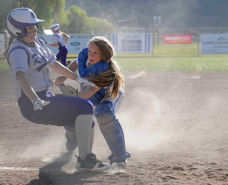 by: LON AUSTIN/CENTRAL OREGONIAN - Aspen Christiansen tags a Ridgeview runner out at home during the second game of the Cowgirls' doubleheader Wednesday afternoon with the Ravens.