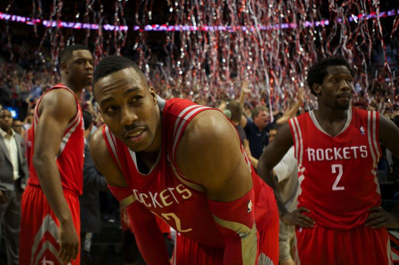 by: TRIBUNE PHOTO: JAIME VALDEZ - Houston Rockets players (from left) Terrence Jones, Dwight Howard and Patrick Beverley get ready to leave the court at Moda Center as fans celebrate the Trail Blazers' victory that closed out the NBA first-round series in Portland's favor, 4-2.