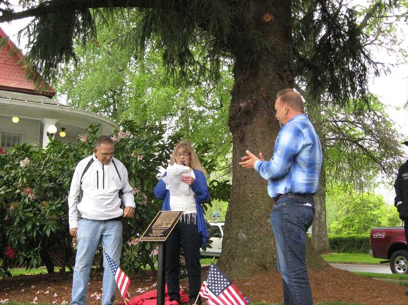 by: GAZETTE PHOTO: RAY PITZ - Tess Kies, center, dedicates a bronze plaque in honor of former Sherwood Police Chief Delbert Stanislowski on May 3 as his sons, Bob and Scott Stanislowski, look on.