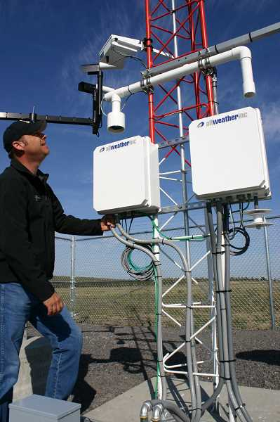 by: JASON CHANEY - Airport manager Kelly Coffelt examines the new weather system installed at the Prineville Airport.