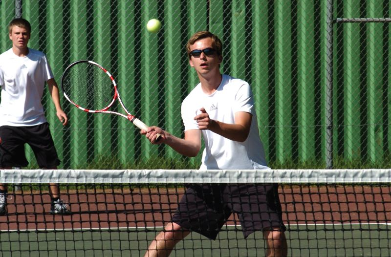 by: ESTACADA NEWS: PARKER LEE - Estacadas Benton Wilbur makes a volley at the net during a doubles match last week against North Marion.