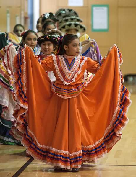 by: SPOKESMAN PHOTOS: JOSH KULLA - Nicole Garcia leads a line of dancers from Boones Ferry Primary Schools Folklorico Dance Group into the gymnasium at Boeckman Creek Primary School. The dancers performed as part of both schools Day of the children celebrations.
