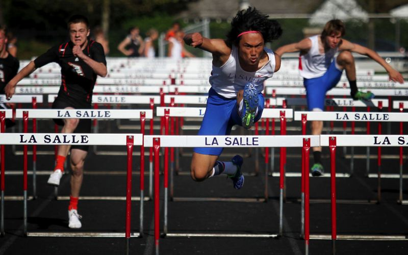 by: JON HOUSE - La Salle senior Ben Hortaleza (center) heads for a Class 5A states best clocking of 14.95 in the high hurdles during last weeks dual meet with Gladstone.