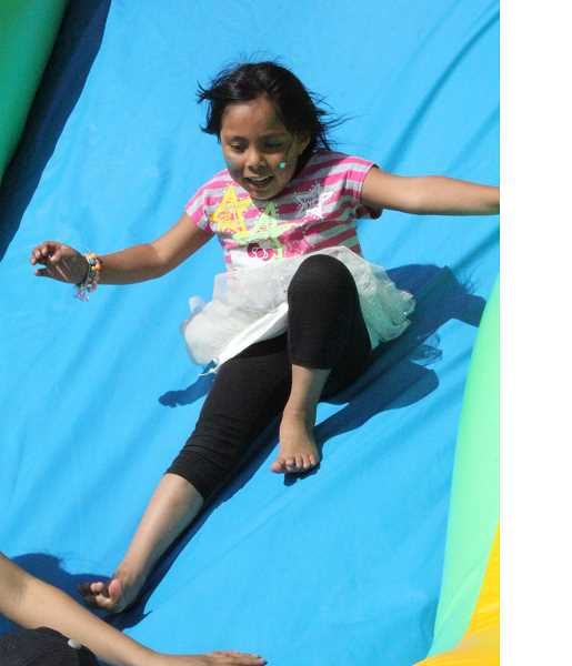 by: LINDSAY KEEFER - A little girl avoids a collision at the base of the bouncy house slide outside Chemeketa Community College in Woodburn Friday.