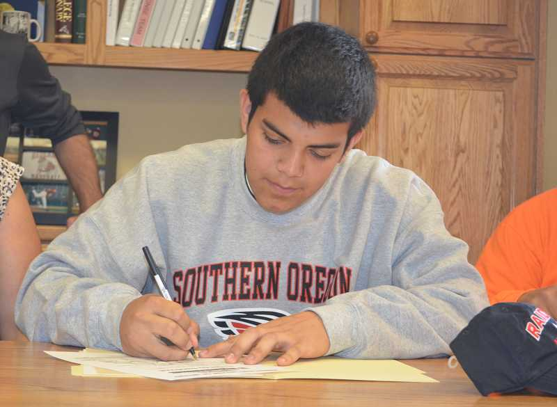 by: JEFF GOODMAN / PAMPLIN MEDIA GROUP - Alejandro Sandoval signs a letter of intent May 5 at Canby High School to join the Southern Oregon wrestling program. Sandoval took second place in the heavyweight division at the state tournament this year.
