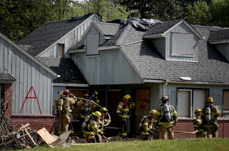 by: TIMES PHOTO: JONATHAN HOUSE - Tualatin Valley Fire & Rescue firefighter recruits practice a test burn on an old house on Southwest Denney Road.