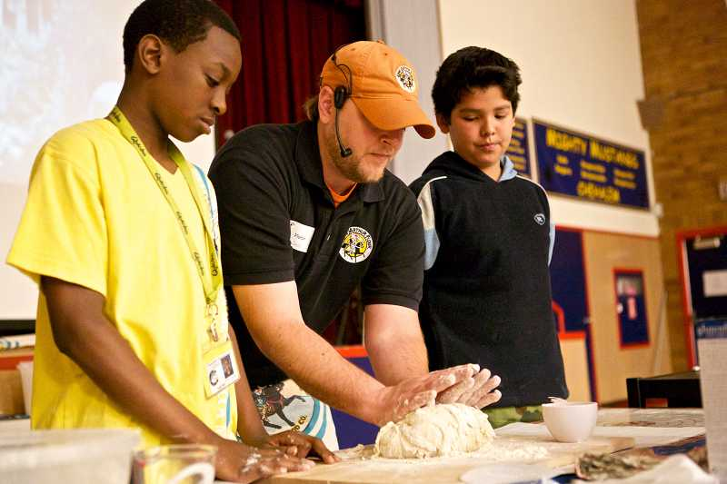 by: TIMES PHOTO: JAIME VALDEZ - Nate Sandel, an instructor with King Arthur Flour's Life Skills Bread Baking Program, shows fifth-graders Wayne McKinney and Esteban Hernandez Baez how to knead dough during an assembly at Chehalem Elementary School.
