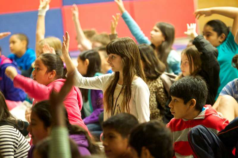 by: TIMES PHOTO: JAIME VALDEZ - Students at Chehalem Elementary School raise their hands to answer a question from Nate Sandel, an instructor in King Arthur Flour's Life Skills Bread Baking Program.