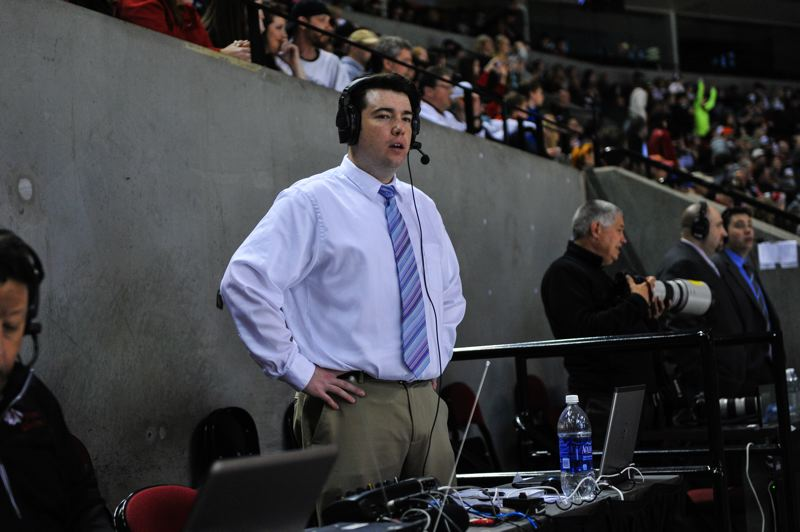 by: COURTESY OF JOHN LARIVIERE - Todd Vrooman checks out the action on the ice as he delivers radio play-by-play of an Portland Winterhawks-Edmonton Oil Kings Western Hockey League finals game.