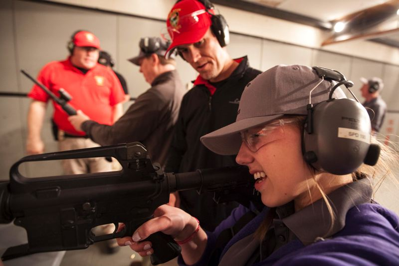 by: THE TIMES: JEFFREY BALL - Caitlin Feldman shoots a rifle for the first time during The Tualatin Police Experience.