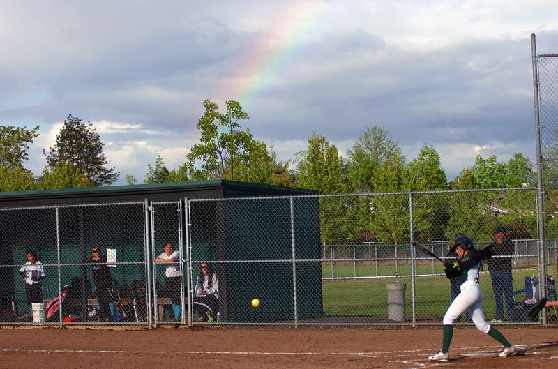 by: DAN BROOD - UNDER THE RAINBOW -- With a rainbow overhead, Tigard junior Kayla Saldana (right) puts the ball in play during the Tigers' win over Century.