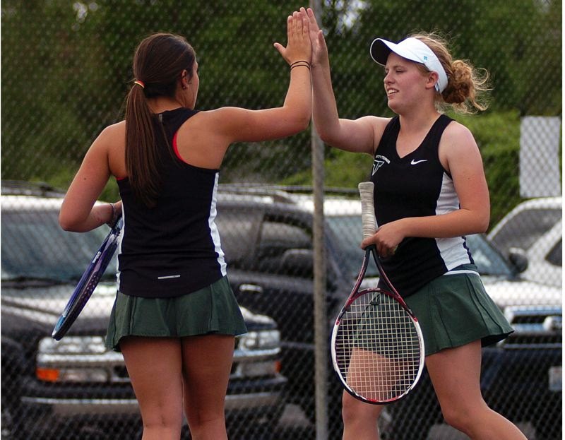 by: DAN BROOD - HIGH FIVE -- Tigard's Hannah Portwood (left) and Carrie Williams celebrate after scoring a point during their victory in No. 1 doubles play in Monday's match with Newberg.