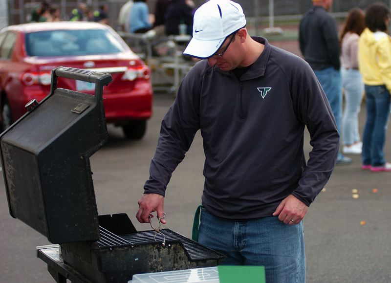 by: DAN BROOD - WORKING THE GRILL -- Tigard girls tennis coach Matt Rubrecht tends over the barbecue as part of the team's Community Day on Monday.