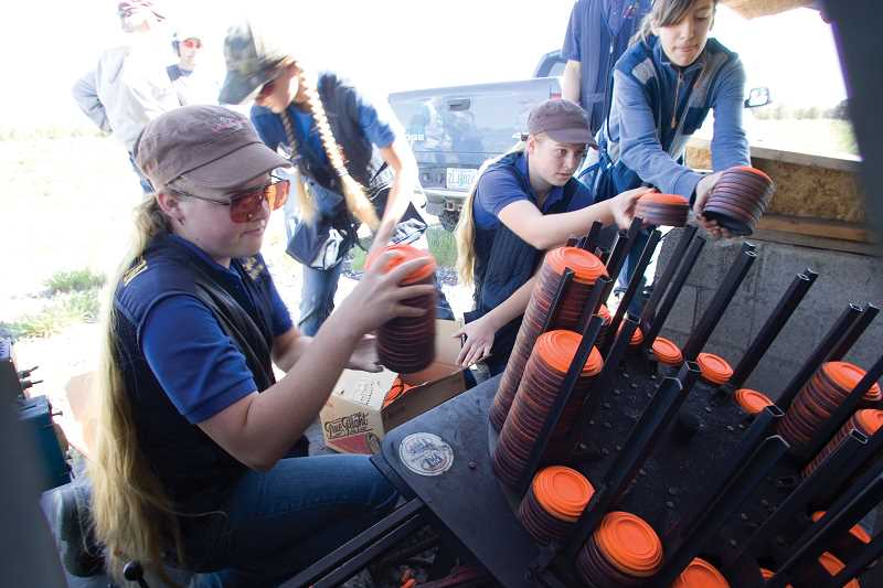 by: KEVIN SPERL - From left, Kayla Pieren, Karinda Pieren and Emily Leavitt load up the sporting clay trap machine before practice on Wednesday.