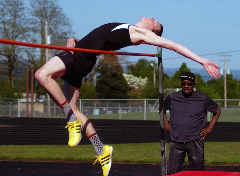 by: DAN BROOD - BIG BEN -- Sherwood junior Ben Milligan takes off in high jump competition in last week's meet at Parkrose.