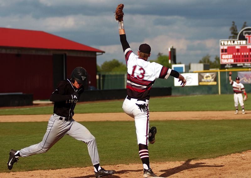 by: DAN BROOD - THE STRETCH -- Tualatin junior first baseman Jacob Bennett (right) reaches high to grab the ball right before Tigard's Brady McGetrick gets to the base in Tuesday's game.