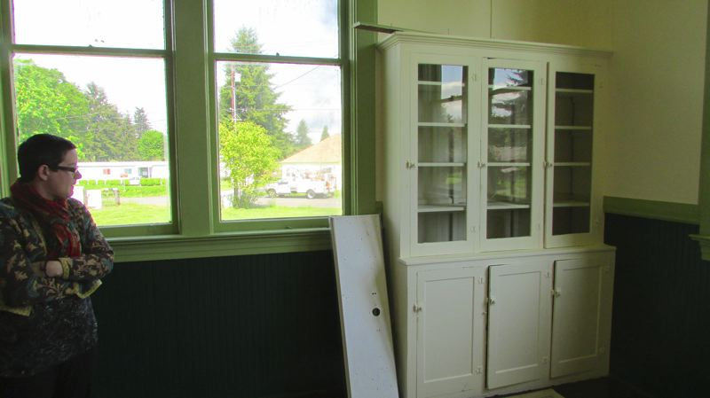 by: MARK MILLER - This built-in cabinet in one of the Deer Island School classrooms will be repaired and restored, according to Jason Dunn, who intends to convert the corner of the room into a guest bedroom. Also in frame is Dunn's partner, Diane Johnson.