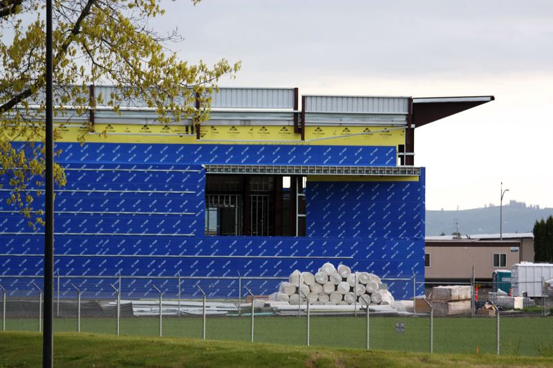 by: HILLSBORO TRIBUNE PHOTO: DOUG BURKHARDT - A new hangar is being built on the east side of the airport, reflecting the increased activity at the Hillsboro Airport. Airport officials want to build a new runway to help alleviate congestion at the facility.