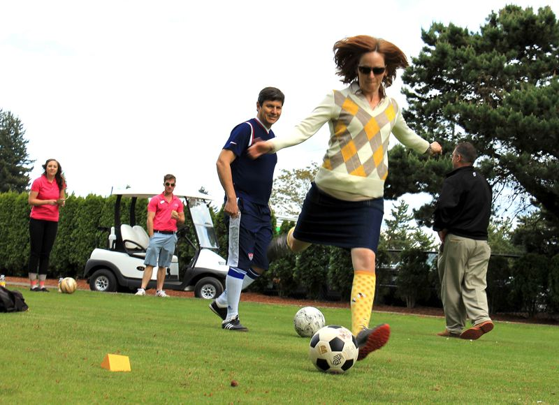 by: OUTLOOK PHOTO: CARI HACHMANN - Kathleen Brennan Hunter, natural areas program director at Metro, goes in for the kick at the opening of a footgolf course at Glendoveer Golf Course in East Portland.