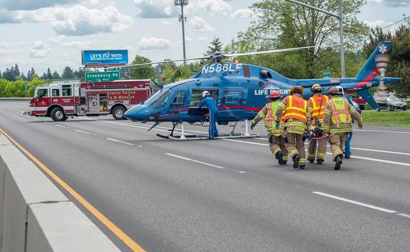 by: TVF&R - TVF&R firefighters transport the driver of a serious single vehicle crash to a waiting Life Flight helicopter.