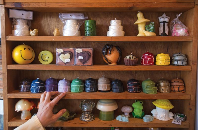 by: PAMPLIN MEDIA PHOTO: JONATHAN HOUSE  - Camelias shelves are stocked with her re-created candle art. Other wax products are recycled into blocks.