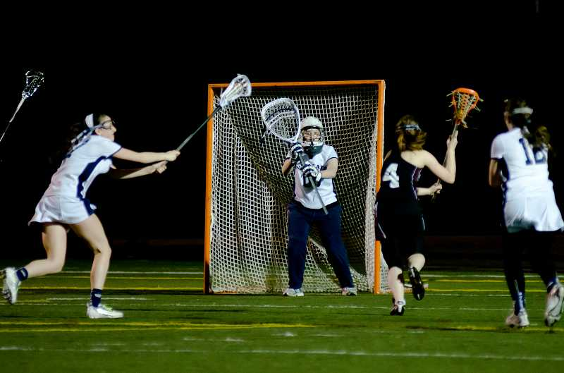 by: GREG ARTMAN - Senior goalkeeper Olivia Chase (center) and the Wilsonville girls lacrosse team captured a conference championship for the second year in a row. The Wildcats, who won all 12 of their league games, will host Beaverton in a playoff game May 14 at Randall Stadium.