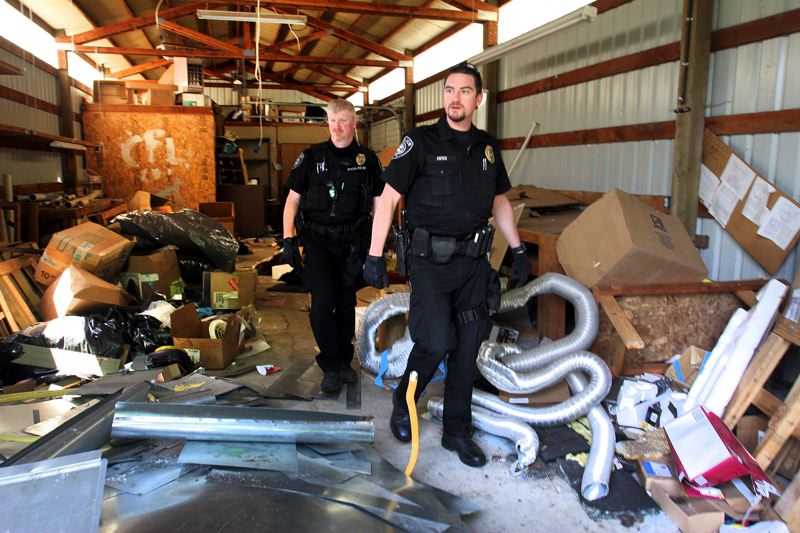 by: OUTLOOK PHOTO: JIM CLARK - Officers Jim Leake, left, and Dan Estes walk through a deserted garage that had been locked but was broken into. The officers found a homeless persons cart that had not been there on their last visit.