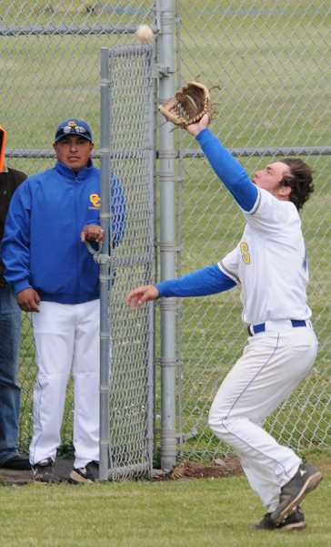 by: LON AUSTIN/CENTRAL OREGONIAN - Crook County third baseman Dylan Blasius catches a foul ball near the fence while Crook County Head Coach Frank Martinez looks on. The Cowboys lost to the Bend Lava Bears 17-3 in the contest as Bend completed a three-game sweep of Crook County.