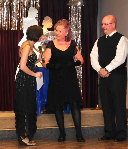by: CONTRIBUTED PHOTO: CARL TEBBENS - Carla Piluso, center, former Gresham chief of police and candidate for House District 50, answers questions from co-emcee Kathy Thienes with her dance partner, John Copeland, right, after competing in the annual Dancing With the Elks competition.