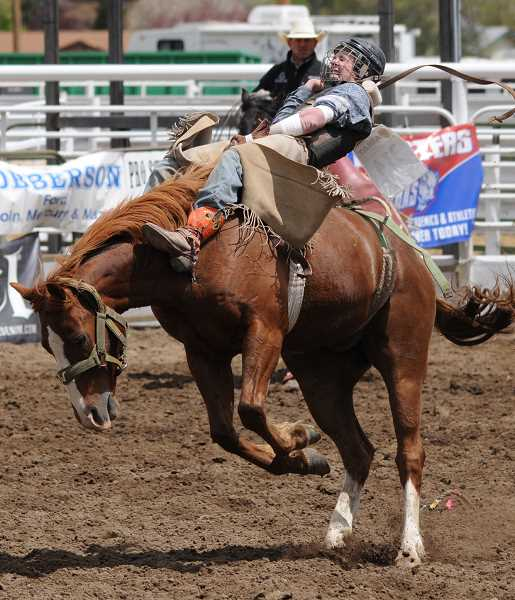 by: LON AUSTIN/CENTRAL OREGONIAN - Brent Bannon strains to finish his bareback ride on Saturday. Bannon won the go round with a score of 61, and also won the average in the event.