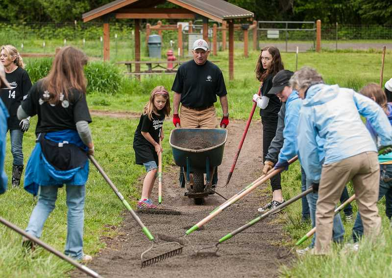 by: SPOKESMAN PHOTOS: JOSH KULLA - Wilsonville Parks and Recreation Director Stan Sherer deposits a load of gravel on a path in the Memorial Park dog park as part of a WERK Day cleanup effort.