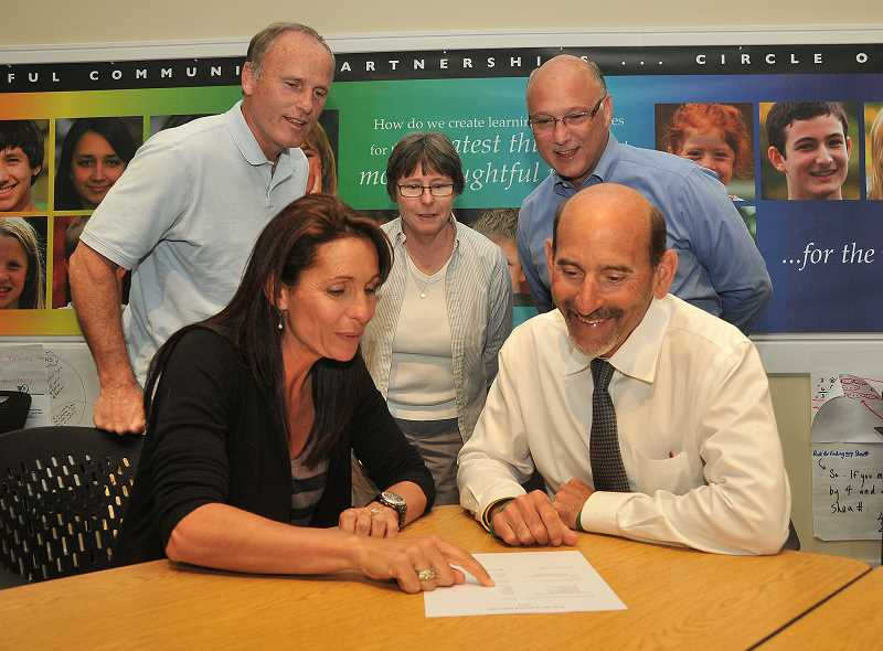 by: FILE PHOTO: VERN UYETAKE - Last May, Michelle Tonkin delivered checks worth more than $20,000 to West Linn-Wilsonville School groups. Shown here are Michelle Tonkin and Superintendent Bill Rhoades, seated. Standing, from left, Wilsonville High School's athletic director, Dennis Burke, Music and Art Partner's treasurer Patti Millage, and the WL-WV Education Foundation's president, Jay Puppo.