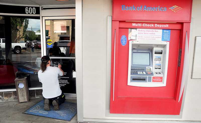 by: GARY ALLEN - Moving on - A worker begins scraping the branch information off Bank of America's front door on Friday afternoon. The bank's Newberg location has closed and its employees, for the most part, are relocating to various branches in Oregon and Arizona.