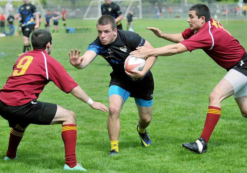 by: SETH GORDON - Strike a pose - Senior Jacob Hooker attempts to maneuver past two Central Catholic defenders Saturday during Newberg's 27-15 win at Delta Park. The Tigers will face Lincoln Saturday in the Rugby Oregon Boys Varsity Premiership Plate final.