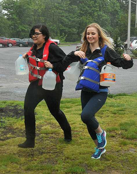 by: REVIEW PHOTO: VERN UYETAKE - Isabella Garcia, left, and Mercedes Grice see what it like to run carrying the weight equivalent to a suit of armor.