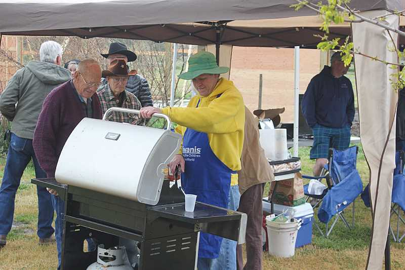 by: JEFF WILSON - Kiwanis member Mike Ahern serves hotdogs to the crowd.