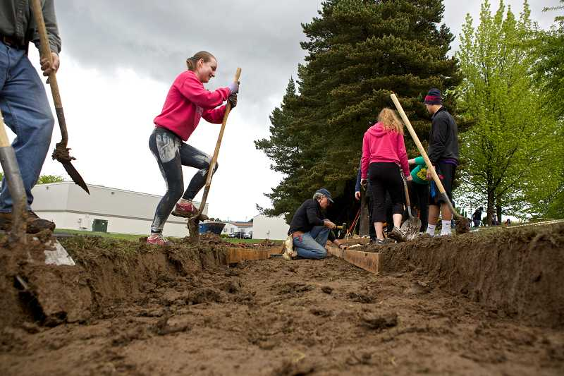 by: TIMES PHOTO: JAIME VALDEZ - Olivia Rohret, Sunset High School junior, shovels dirt on a path that will lead to the school's track during the school's service day in honor of Sunset grad Army Spc. John A. Pelham.