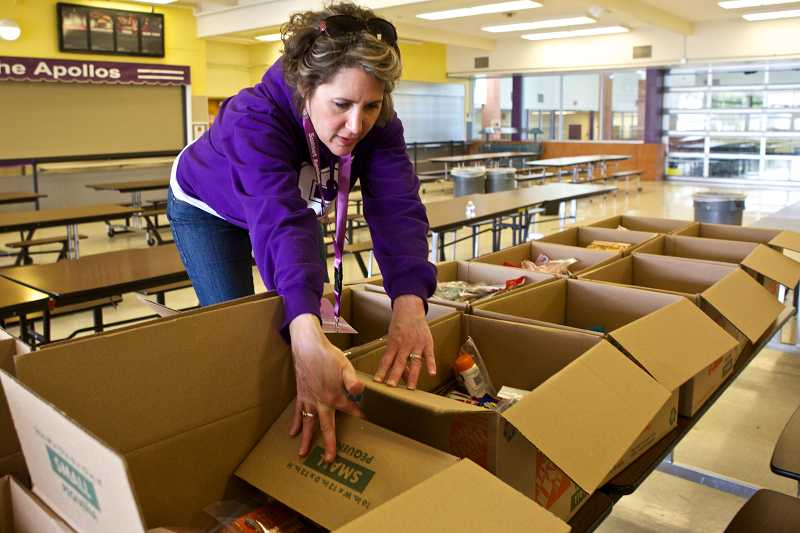by: TIMES PHOTO: JAIME VALDEZ - Tracy Nordyke, a member of the Community Engagement Committee at Sunset High School, shows the care boxes full of of goodies that will be sent to an upcoming pre-deployment event for two Oregon National Guard units in Seaside.